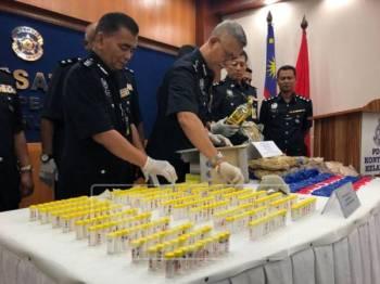 Hasanuddin (dua, kiri) melihat dadah yang dirampas daripada suspek.