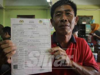 Chin Chyuan menunjukkan sijil kelahiran anak angkatnya.