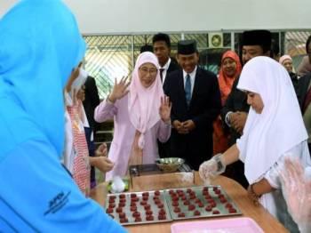 Wan Azizah dibawa melawat kelas kemahiran yang diberikan kepada golongan kurang upaya ketika melakukan lawatan di Pusat Bahagia Brunei hari ini. - Foto Bernama