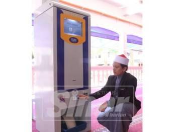 Muhammad Khairul Razikin menunjukkan cara mesin ATM beras beroperasi.