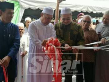 Ahmad (dua, kiri) memotong reben sebagai tanda perasmian Madrasah Haji Ibrahim, Kampung Jalan Bunut Susu.