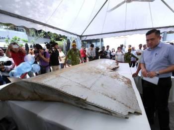 Anthony Loke  melihat serpihan sayap bangkai pesawat MH370 yang dipamerkan sempena Majlis Memperingati Tragedi MH370 di ruang legar Publika hari ini.  - Foto Bernama