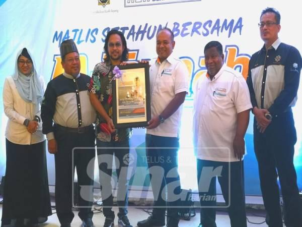 KHAIRUL (tiga, kanan) menyerahkan cenderahati kepada Duta M-Jannah, Mawi sambil disaksikan Mohd Zainal (dua dari kiri) dan Ketua Pegawai Eksekutif Bumijez, Ab Halim Hamzah (kanan).