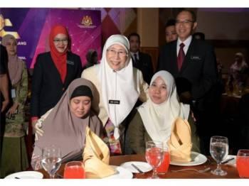 Wan Azizah (tengah) beramah mesra bersama Orang Kelainan Upaya Nor Asniza Ibrahim (duduk, kiri) dan Nura Adila Mohd Rashidi (duduk, kanan) pada Majlis Anugerah Perkhidmatan Cemerlang (APC) Tahun 2018 di Pusat Konvensyen Antarabangsa Putrajaya (PICC) hari ini. - Foto Bernama