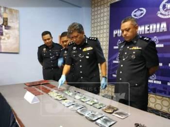 Ismadi (tengah) menunjukkan dadah yang dirampas dalam satu serbuan di sebuah apartmen di Puchong malam semalam.