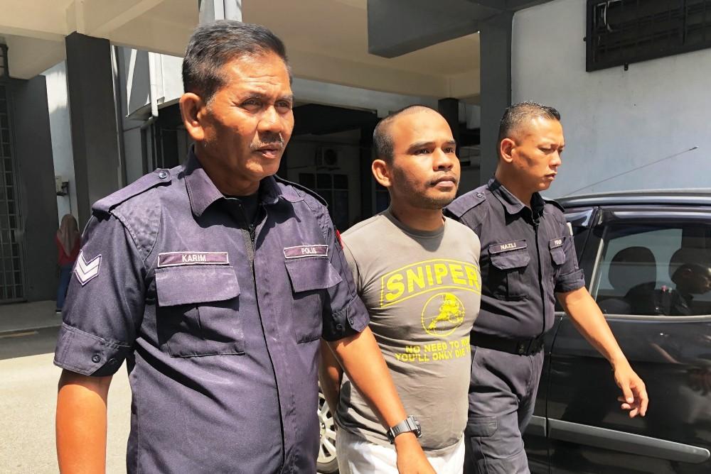 Anggota polis mengiringi Mohd Roslan (tengah) ke Mahkamah Sesyen, hari ini.