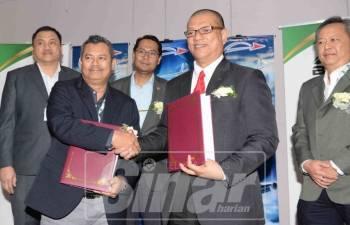 Mohd Asmirul (tengah) menyaksikan pertukaran dokumen antara Abdul Wahab (kanan) dan Nazaruddin (kiri) selepas menandatangani MoU.