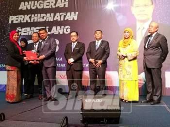 Saifuddin (lima dari kanan) menyampaikan anugerah kepada salah seorang penerima pada majlis itu.