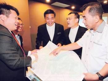 Kok Kiew (tiga, kanan) melihat pelan Melaka ketika program FGD bagi kajian pengurusan MPKK dan sempadan kampung di Hotel Mudzaffar, semalam.