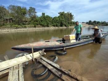 Seorang pembawa bot tambang, Din Mamat, 50, (kanan) menceritakan dia perlu berhati-hati kerana bimbang terlanggar bongkah kayu atau batu yang ada di dasar Sungai Golok. - Foto Bernama