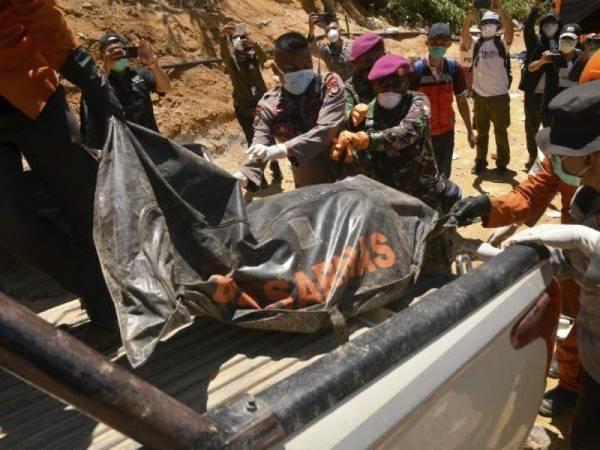 Pasukan penyelamat mengangkat beg mayat mangsa runtuhan lombong emas haram di Bolaang Mongondow di Sulawesi Utara.