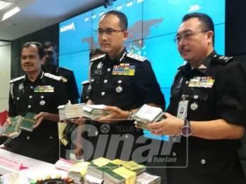 Khairul Dzaimee menunjukan pasport yang dirampas dalam dua serbuan di Ampang dan Subang Jaya.