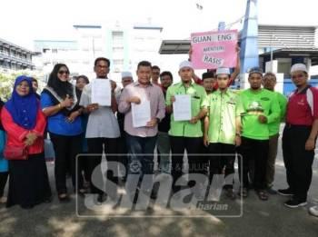 Mohd Norhiesam (lima, kiri) bersama Ellangovan (empat, kiri) dan Abdul Mushawwir (empat, kanan) menunjukkan laporan polis yang dibuat mereka terhadap Menteri Kewangan, Lim Guan Eng.