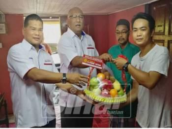 Kamari Zaman (dua, kiri) menyerahkan sumbangan daripada CBP kepada wakil keluarga mangsa, Mohd Fazuan (dua, kanan) sambil diiringi Mohd Nor (kiri).