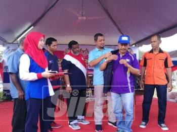 Dr Sahruddin memakaikan ves sukarelawan Combi kepada salah seorang wakil peserta pada program tersebut, hari ini.