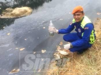 Anggota Angkatan Pertahanan Awam Jasin Prebet (PA), Asyraf Mislan,22, menunjukkan air yang kehitaman sejak semalam.