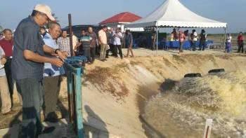 Mohd Sallehuddin (kiri) membuka pintu kawalan air di Stesen Pam Tali Air Bedang Nara.