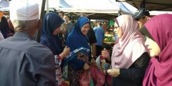 Fuziah (dua, kanan) beramah mesra bersama pengunjung pada program Santuni Wanita sempena Hari Wanita Sedunia di Pasar Tani Mega Kuantan, di sini, hari ini.