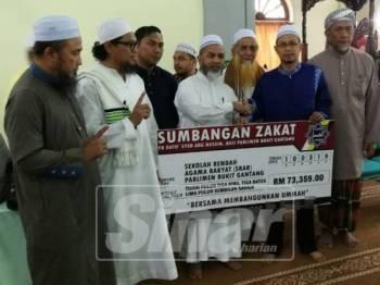 Syed Abu Hussin (tengah) menyerahkan cek replika sumbangan SRAR Parlimen Bukit Gantang bernilai RM73,359 kepada wakil SRAR Parlimen itu di Masjid Rahmaniah, Trong hari ini.