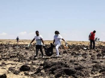Pekerja penyelamat mengangkat mayat di lokasi pesawat Ethiopia Airlines terhempas pagi semalam, berhampiran bandar Bishoftu. - FOTO AFP