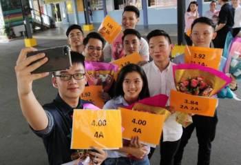 Jian Tin (kiri) dan Hui Mein (kanan) berswafoto bersama rakan rakan lain yang cemerlang STPM.