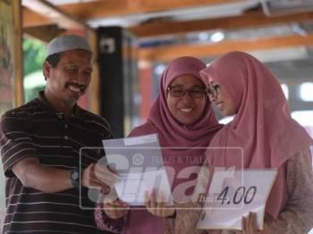 Nur Syahidah (kanan) bersama ibunya, Norhidayah Mustafa, 50, dan Hassan Salleh, 53 yang menemaninya ketika mengambil keputusan peperiksaan di SMA (A) Sultan Zainal Abidin, hari ini.