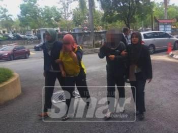 Kedua-dua suspek diiring pegawai SPRM sebaik tiba di mahkamah.