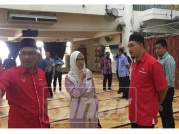 Abdul Aziz (kanan) berbual dengan Naimah mengenai kerosakan Pusat Islam PSAS yang dipukul ribut semalam.
