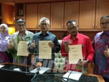 Mohd Salleh (tengah) menunjukkan keputusan SPM 2018.