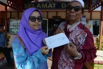 Khairul Najwa bersama bapanya ketika mengambil keputusan SPM.