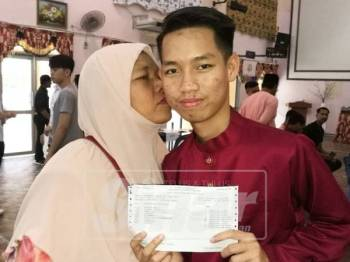 Nor Ain mencium anaknya, Mohd Adham yang mendapat 9A SPM di SMK Dato Penggawa Barat.