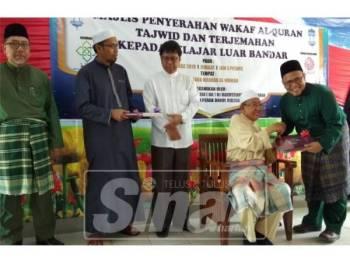 Harussani (duduk) menyerahkan naskhah al-Quran kepada wakil SABK Maahad Al-Ummah, Muhammad Hafez Ardhi pada program tersebut.