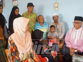 Mahfuz (kanan) berbual dengan ahli keluarga Tarmizi di rumah mereka di Hutan Kampung.