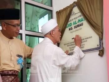 Mohamad Shukri menandatangani plak perasmian Masjid Al Hassan hari ini.