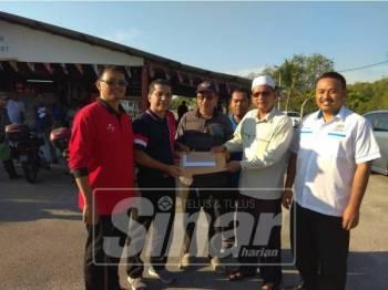 Syed Ibrahim (dua, kiri) menerima kertas kerja daripada Ketua Kampung Kesang, Musa Daud sambil diperhatikan Adun Serom, Dr Ir Faizul Amri Adnan (kanan) dan Penghulu Mukim Serom, Mahathir Abdul Ghani (tiga, kanan).