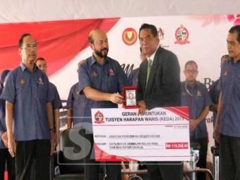 Mukhriz (dua, kiri) menyerahkan replika cek geran peruntukan Tuisyen Harapan Waris (Keda) kepada wakil Jabatan Pendidikan Negeri Kedah, disaksikan Muhd Kameh (kiri).