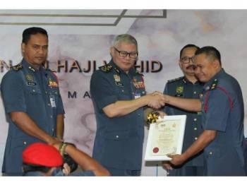 Dari kiri, Nor Hisham dan Mohammad Hamdan ketika menyampaikan anugerah kecemerlangan kepada Komander Operasi Kanan Zon 2, Mohd Arshad Abdullah.
