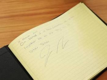 Ardern menandatangani buku takziah buat mangsa serangan pengganas di masjid Christchurch.