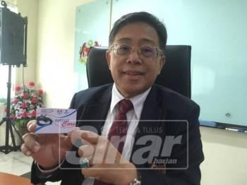 Azih menunjukkan kad MyCuepacsCare yang telah dilancarkan pada tahun 1999 dan memberikan manfaat perubatan kepada penjawat awam.