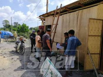 Anggota imigresen membuat pemeriksaan di Kampung Kubang Bujuk, Kuala Terengganu.