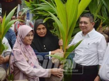 Salahuddin (kanan) menyerahkan benih pokok kelapa kepada penerima.