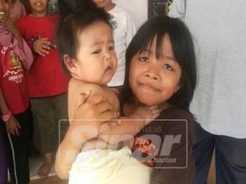 Intan Nabila bersama adiknya yang diselamatkan dalam kebakaran pagi tadi.