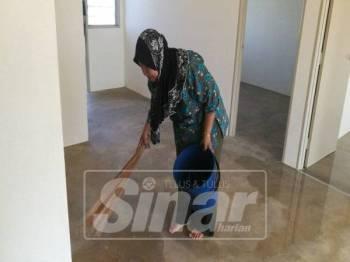 Habibah sedang membersihkan lantai rumahnya.