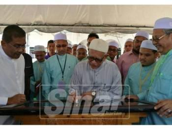 Abdul Hadi (tiga,kanan) ketika menyempurnakan gimik perasmian Pasar Pagi Sabtu semasa Mesyuarat Agung Tahunan Ke-41 Pas Kawasan Rantau Panjang di Dewan Abdul Samad Gul, Pusat Tarbiyah Kawasan Rantau Panjang.
