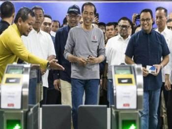 Jokowi (tengah) bersama beberapa pegawai kerajaan menyertai upacara perasmian MRT.