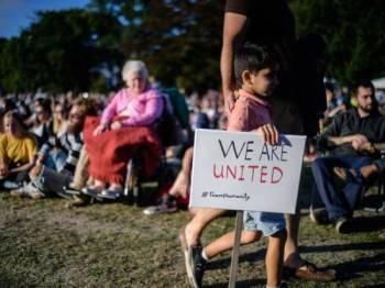 Seorang kanak-kanak memegang plakad bertulis 'Kami Bersatu' ketika menghadiri himpunan mengenang mangsa serangan masjid di Christchurch pada 15 Mac lalu. - Foto AFP