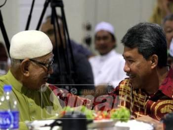 Mohamad berbual mesra dengan Abdul Hadi pada majlis makan malam yang diadakan, di sini, malam tadi. -Foto Syamilah Zulkifli