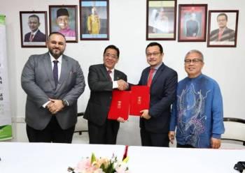 Azizi (dua,kanan) menyerahkan dokumen MOU kepada Dr Nazily di Kampus Kota, di sini.