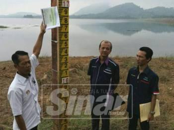 Kamal (kiri) bersama pegawainya ketika meninjau keadaan paras air di empangan Bukit Kwong, Lubok Stol yang ketika ini berada pada tahap serius.
