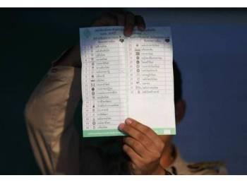 Pegawai EC menunjukkan kertas undi ketika proses kiraan dilakukan.